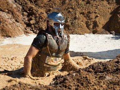 Seorang peserta mengenakan kostum gladiator melintasi lubang lumpur selama lomba lari Strongman Run di kota Paarl, Afrika Selatan, 13 Oktober 2018. Strongman Run adalah lomba lari halang rintang untuk menguji kecepatan dan daya tahan. (RODGER BOSCH/AFP)
