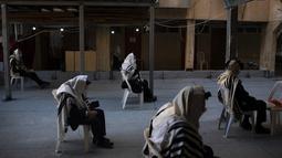 Yahudi Ultra-Ortodoks mengenakan masker dan menjaga jarak sosial saat berdoa selama lockdown nasional di Bnei Brak, Israel, Jumat (8/1/2021). Israel memperketat lockdown nasional dengan membatasi pertemuan publik selama dua minggu mulai Jumat. (AP Photo/Oded Balilty)