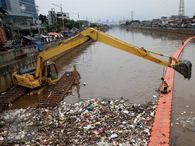 Petugas kebersihkan dibantu alat berat membersihkan sampah di Sungai Kanal Banjir Barat, Jakarta, Senin (14/11). Hujan yang terjadi di hulu Banjir Kanal Barat mengakibatkan meningkatnya debit air yang disertai sampah. (Liputan6.com/Johan Tallo)