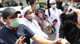 Rizieq Shihab (kedua kiri) sesaat tiba di Mapolda Metro Jaya, Jakarta, Sabtu (12/12/2020). Rizieq Shihab akan menjalani pemeriksan sebagai tersangka penghasutan dan kerumunan di tengah pandemi Covid-19. (Liputan6.com/Helmi Fithriansyah)
