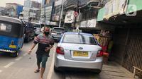 Sebuah taksi terparkir di sekitar trotoar kawasan Jatinegara, Jakarta, Selasa (14/7/2020). Tidak adanya sanksi tegas membuat trotoar yang telah diperlebar tersebut justru dimanfaatkan sebagai lahan parkir liar yang mengganggu ketertiban umum. (Liputan6.com/Immanuel Antonius)