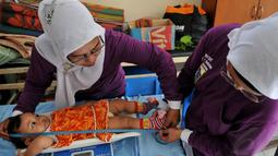Relawan tampak menimbang dan mengukur seorang balita di posyandu Gerogol Selatan, Kebayoran Lama, Jakarta, Selasa (29/4/14) (Liputan6/JohanTallo)