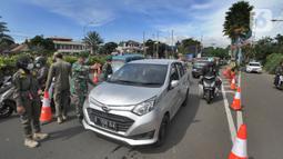 Petugas gabungan Satgas COVID-19 memeriksa kendaraan wisatawan di jalur wisata Puncak, Gadog, Bogor, Jawa Barat, Jumat (12/2/2021). Pemeriksaan dan penyekatan sebagai upaya meminimalisir penyebaran COVID-19 saat libur Tahun Baru Imlek 2572 dan akhir pekan. (merdeka.com/Arie Basuki)