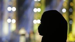 Seorang wanita mengenakan masker untuk membantu mencegah penyebaran virus corona mendengarkan penyanyi terkemuka Saudi Mohammed Abdu saat ia tampil di Super Dome yang baru dibangun, di Jiddah, Arab Saudi (8/7/2021). (AP Photo/Amr Nabil)