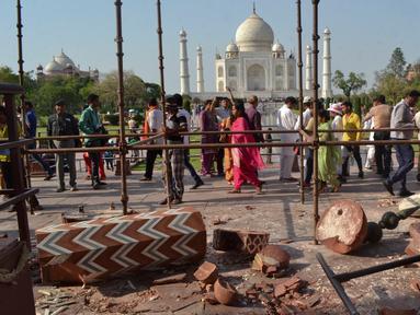 Wisatawan berjalan melewati reruntuhan puing-puing dari pilar Taj Mahal yang roboh di pintu masuk bangunan ikonik tersebut di Agra, India, Kamis (12/4). Dua buah pilar menara Taj Mahal rusak akibat dihantam angin kencang. (AP/Pawan Sharma)
