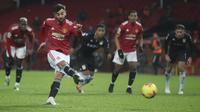 Gelandang Manchester United, Bruno Fernandes saat mencetak gol lewat titik penalti pada menit 61 ke gawang Aston Villa pada pertandingan lanjutan Liga Inggris di stadion Old Trafford, Inggris  (2/1/2021). MU menang tipis atas Aston Villa 2-1. (Carl Recine/ Pool via AP)
