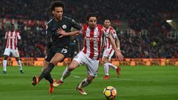 Pemain Manchester City,Leroy Sane (kiri) membayangi pemain Stoke City, Joe Allen (kanan) pada lanjutan Premier League di Bet 365 Stadium, Stoke, (13/3/2018). Manchester City menang 2-0. (AFP/Paul Ellis)