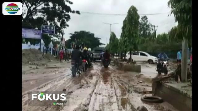 Selain lumpur di kanan kiri jalan, juga terlihat batang kayu yang terbawa saat banjir bandang.