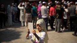 Seorang anak perempuan mengambil gambar seusai pelaksanaan salat Idul Fitri di masjid Niujie, Beijing, 26 Juni 2017. Umat muslim di berbagai penjuru dunia merayakan Idul Fitri, yang menandai berakhirnya bulan suci Ramadan. (AP Photo/Mark Schiefelbein)