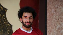 Pesepakbola Irak Hussein Ali berpose mengenakan kostum Liverpool di ibukota Baghdad (4/6). Dengan jenggot hitamnya dan rambut keriting, Hussein Ali sering disangka sebagai salah satu pemain top dunia Mohamed Salah asal Mesir. (AFP Photo/Sabah Arar)