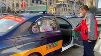 Sopir taksi menyemprotkan cairan disinfektan. (Xinhuanet/Zing)