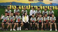 12 anak laki-laki dan pelatih sepak bola mereka, yang diselamatkan dari gua banjir di Thailand tampil ke muka publik untuk pertama kalinya di Chiang Rai, Rabu (18/7). Mereka memasuki ruang konferensi pers dengan memakai seragam. (LILLIAN SUWANRUMPHA /AFP)