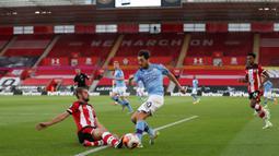 Gelandang Manchester City, Bernardo Silva (tengah) berebut bola dengan bek Southampton Jack Stephens dalam lanjutan Liga Inggris di St. Mary Stadium, Minggu (5/7/2020).  Manchester City gagal memetik poin penuh setelah kalah tipis 0-1 saat bertandang ke markas Southamtpon. (Catherine Ivill/POOL/AFP)