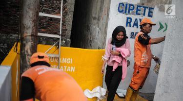 Petugas PPSU menyelesaikan pengerjaan jalur peningkatan aksesibilitas jalan lokal dan kampung menuju Stasiun MRT di Gang Teladan, Cipete Raya, Jakarta, Senin (2/9/2019). Hal ini untuk meningkatkan keamanan bagi pejalan kaki dan pesepeda menuju Stasiun MRT Cipete Raya. (Liputan6.com/Faizal Fanani)