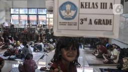 Aktivitas warga korban banjir saat mengungsi di salah satu ruang kelas SDN 01 Kampung Melayu, Jakarta, Minggu (21/2/2021). Selama pandemi virus corona, pihak kelurahan menyiapkan pengungsian di lantai 1 dan 2 serta membatasi 50 persen kapasitas pengungsi. (merdeka.com/Iqbal S Nugroho)