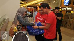 Tim Tempo Scan Love Earth memberikan pengunjung sebuah tas jinjing sebagai bentuk kepedulian untuk mengurangi sampah plastik, Jakarta, Kamis (28/4). (Liputan6.com/Gempur M Surya)