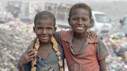 Dua anak laki-laki berpose saat diambil gambarnya di tempat pembuangan sampah, dimana mereka mengumpulkan sampah untuk didaur ulang, di kota Houdieda, Yaman, Rabu (20/1). (REUTERS/Abduljabbar Zeyad)