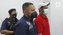 Petugas membawa artis peran Rio Reifan untuk dihadirkan dalam rilis kasus narkoba di Polres Metro Jakarta Pusat, Rabu (21/4/2021). Rio Reifan tertangkap basah ketika polisi menggeledah rumahnya saat memesan sabu melalui ojek online dengan berat 1 gram. (Liputan6com/Herman Zakharia)