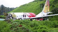 Petugas berdiri di atas puing-puing pesawat Air India Express yang tergelincir dari landasan pacu saat mendarat di Kozhikode, negara bagian Kerala, India, Sabtu, (8/8/2020). Akibat musibah tersebut sedikitnya 17 orang tewas. (AP Photo/C.K.Thanseer)