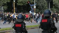 Seorang demonstran melemparkan suar saat protes terhadap peraturan Covid-19 di Melbourne (21/9/2021). Ribuan orang membuat kekacauan dan bentrok dengan polisi di kota dan mengambil alih jalan raya utama Melbourne saat protes terjadi. (AFP/STR)