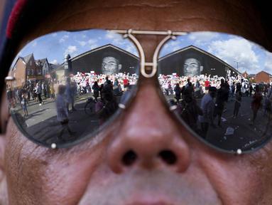 Ratusan orang berkumpul untuk menggelar aksi anti Rasisme di depan mural wajah pemain Timnas Inggris, Marcus Rashford di Withingston, Manchester. (Foto:AP/Jon Super)