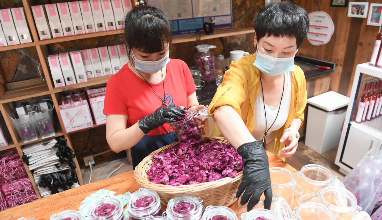 Para staf mengemas kelopak bunga mawar di Wilayah Daixi, Kota Huzhou, Provinsi Zhejiang, China timur (9/6/2020). Wilayah Daixi telah mengembangkan industri kosmetik sejak 2015. (Xinhua/Weng Xinyang)