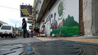 Mural yang dibuat pada tembok bangunan di Jalan Stasiun Kereta Api tersebut memiliki makna sebagai ajakan hidup sehat bagi warga Medan atas ancaman Covid-19 yang disimbolkan sebagai virus monster.