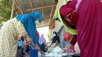 Aktivitas Ibu-ibu dengan gerakan 'Sigi Mosi Jagai' di Desa Langaleso, Sigi saat memasak untuk kebutuhan makanan warga yang menjalani isolasi mandiri, Senin (16/8/2021). (Foto: Heri Susanto/ Liputan6.com).