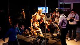 Pengunjung melihat salah satu karya seni yang dipajang dalam pameran anatomi tubuh manusia bertajuk 'Body Worlds' di Moskow, Rusia (24/3/2021). Otoritas Rusia tengah melakukan penyelidikan terkait pameran tersebut. (AFP/Dimitar Dilkoff)