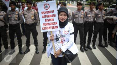 Seorang dokter membawa poster saat melakukan aksi unjuk rasa di Ibu Kota hari ini, Senin (24/10). Demo itu untuk menuntut pemerintah agar membatalkan Program Dokter Layanan Primer (DLP). (Liputan6.com/Faizal Fanani)