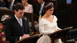 Putri Eugenie dan Jack Brooksbank saat melangsungkan proses pemberkatan nikah di Kapel St. George, Windsor Castle, London, Inggris,  Jumat (12/10). Pernikahan ini dihadiri Ratu Elizabeth II, bangsawan senior dan selebritas. (Jonathan Brady, Pool via AP)