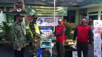 Area Manager PGE Area Karaha Roy Bandoro Swandaru tengah menyerahkan sejumlah fasilitas kesehatan kepada Komandan Rayon Militer (Danramil) 1204/Ciawi Mayor Inf Deni Zenal Muttaqin, dalam upaya memutus penyebaran Covid-19. (Liputan6.com/Jayadi Supriadin)