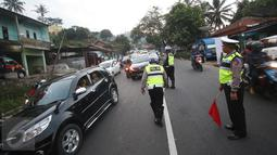 Petugas kepolisian mengatur arus lalu lintas di Simpang Nagreg, Jawa Barat, Sabtu (2/7). Polisi memberlakukan sistem rekayasa lalu lintas untuk menghindari kemacetan yang menuju ke Garut dan Tasik. (Liputan6.com/Immanuel Antonius)