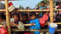 Anak-anak pengungsi muslim Rohingya menunggu bantuan makanan di kamp pengungsi Thankhali di Distrik Ukhia, Bangladesh, (12/1). Mereka melarikan diri bersama orangtuanya saat konflik pecah di Myanmar. (Munir UZ ZAMAN/AFP)