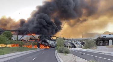 Asap membumbung saat kereta barang tergelincir dan terbakar di jembatan Danau Kota Tempe, Arizona, Amerika Serikat, Rabu (29/7/2020). Tidak ada korban luka dalam kecelakaan yang menurut seorang saksi digambarkan sebagai 'pemandangan neraka' tersebut. (Daniel Coronado via AP)