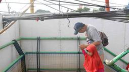 Pejalan kaki melintasi jembatan penyeberangan orang yang terhalang instalasi kabel di Depok, Jawa Barat, Sabtu (8/12). Selain mengganggu kenyamanan, keberadaan instalasi kabel semrawut tersebut membahayakan pejalan kaki. (Liputan6.com/Immanuel Antonius)