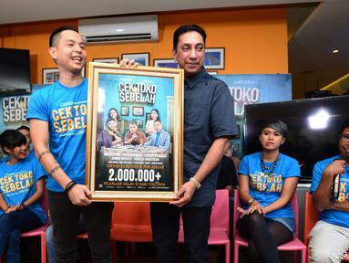 Aktor dan sutradara Ernest Prakasa bersama Produser Starvision Chand Parwez berfoto bareng dengan piagam 2 juta penonton saat jumpa pers Film Cek Toko Sebelah di kawasan Sarinah, Jakarta, Senin (16/1). (Liputan6.com/Herman Zakharia)