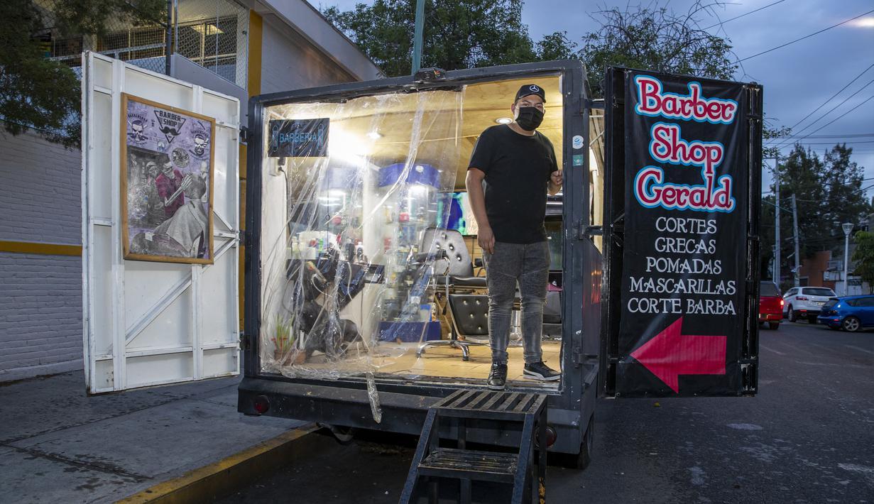 Barber Meksiko Gerardo berpose dalam salon rambut keliling miliknya di Mexico City, Meksiko, 6 Agustus 2020. Gerardo mengubah sebuah mobil van menjadi salon rambut keliling yang menawarkan jasa pangkas rambut kepada warga Mexico City di tengah pandemi COVID-19. (Xinhua/Ricardo Flores)