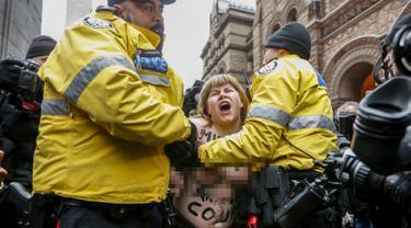 Pengunjuk rasa bertelanjang dada ditahan oleh polisi setelah seorang hakim Ontario memutuskan mantan penyiar radio Kanada, Jian Ghomeshi tidak bersalah atas 4 tuduhan pelecehan seksual dan penyerangan di Toronto, Kanada (24/3/2016). (Reuters/Mark Blinch)