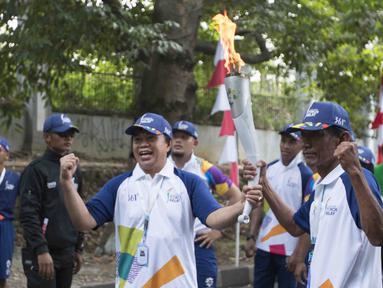 Legenda olahraga Indonesia, Ellyas Pical dan Sutiyono, saat pawai obor Asian Games 2018 di Bogor, Jawa Barat, Selasa (14/8/2018). Api obor yang datang dari Cianjur itu langsung diarak mengelilingi jalanan protokol Kota Bogor. (Bola.com/Reza Bachtiar)