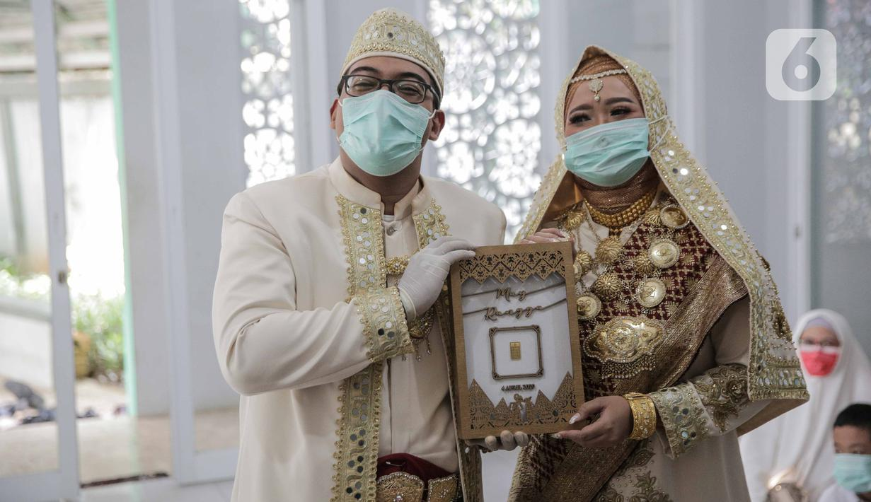 Sepasang pengantin seusai melaksanakan akad nikah di kawasan Pancoran, Jakarta, Rabu (1/4/2020). Pasangan tersebut menggelar pernikahan yang hanya dihadiri pihak keluarga mempelai guna menghindari pertemuan dengan orang banyak dan meminimalkan penyebaran COVID-19. (Liputan6.com/Faizal Fanani)