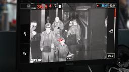 Petugas kesehatan memantau suhu tubuh penumpang yang tiba dengan 'thermal scanner' di Bandara Internasional Kuala Lumpur, Sepang, pada Selasa (21/1/2020). Pemerintah Malaysia mulai mengoperasikan alat pemindai suhu tubuh merespons penyebaran virus korona yang kian masif di China. (MOHD RASFAN/AFP)