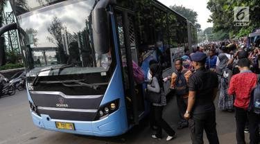 Masyarakat menaiki bus Transjakarta di depan Cibubur Junction, Jakarta, Senin (16/4). Imbas penerapan penerapan Ganjil-Genap di ruas Gerbang Tol Cibubur 2 sebagaian masyarakat memilih menggunakan Transjakarta. (Liputan6.com/Faizal Fanani)