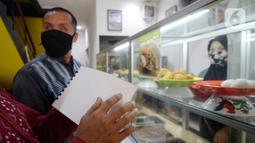 Pengunjung tuna netra memilih menu makanan menggunakan panduan buku braille di Warteg FAST, Graha Raya Bintaro, Tangerang Selatan, Banten, Kamis (3/12/2020). Hari ini diperingati Hari Penyandang Disabilitas Internasional. (merdeka.com/Dwi Narwoko)