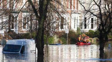 Tim regu penyelamat menyisir lokasi pemukiman warga yang terendam banjir menggunakan perahu karet di York, Inggris utara, Minggu (27/12). Banjir akibat luapan sungai Ouse yang telah memperburuk sejumlah wilayah Inggris utara. (REUTERS/Phil Noble)
