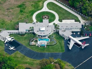 Apa yang biasanya terparkir di garasi seseorang? Mobil supermewah? Yacht? Selebritas Hollywood John Travolta punya pesawat Boeing 707 pribadi di garasi rumahnya, lengkap dengan landasan.(architecturaldesign.com)