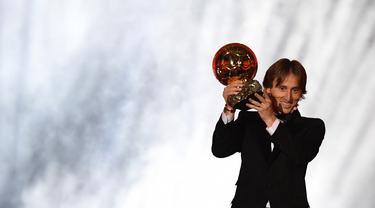 Gelandang Real Madrid asal Kroasia, Luka Modric, menunjukan trofi saat malam penghargaan Ballon d'Or di Paris, Senin (3/12). Dirinya berhasil meraih gelar Ballon d'Or. (AFP/Franck Fife)