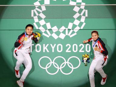 Pasangan Indonesia, Apriyani Rahayu (kiri) dan Greysia Polii Indonesia berpose di lapangan dengan medali emas bulu tangkis ganda putri mereka selama Olimpiade Tokyo 2020 di Musashino Forest Sports Plaza di Tokyo pada 2 Agustus 2021. (AFP/Pool/Lintao Zhang)