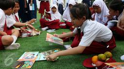 Seorang murid sekolah dasar memilih buku di halaman Istana, Jakarta, Rabu (17/8). Sebanyak 500 pelajar menikmati membaca dan mendengarkan dongeng di halaman istana untuk memperingati Hari Buku Nasional. (Liputan6.com/Angga Yuniar)