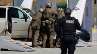 Petugas Polisi Mounted Royal Kanada mengelilingi seorang tersangka di sebuah pom bensin di Enfield, Nova Scotia, Minggu (19/4/2020). Kejadian ini  menjadi aksi pembunuhan mematikan terburuk di negara itu dalam 30 tahun terakhir. (Tim Krochak/The Canadian Press via AP)